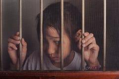 Λυπημένο ασιατικό παιδί που στέκεται πίσω από το παράθυρο οθόνης καλωδίων δυστυχισμένος Στοκ Εικόνες