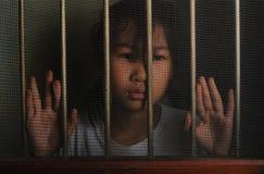 Λυπημένο ασιατικό παιδί που στέκεται πίσω από το παράθυρο οθόνης καλωδίων στο σκοτεινό μ Στοκ Εικόνα