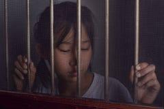 Λυπημένο ασιατικό παιδί που στέκεται πίσω από το παράθυρο οθόνης καλωδίων στη διάσπαση Στοκ Εικόνες