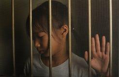 Λυπημένο ασιατικό παιδί που στέκεται πίσω από το παράθυρο οθόνης καλωδίων δυστυχισμένος Στοκ Εικόνα