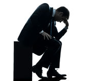 Λυπημένο επιχειρησιακό άτομο που κάθεται τη σκεπτική σκιαγραφία Στοκ εικόνες με δικαίωμα ελεύθερης χρήσης