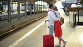 Λυπημένο ερωτευμένο χάδι νεαρών άνδρων και ρητό αντίο στη φίλη του στο σιδηροδρομικό σταθμό πρίν αναχωρεί την ηλιόλουστη ημέρα απόθεμα βίντεο