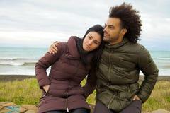Λυπημένο ζεύγος που αγκαλιάζει μπροστά από τον ωκεανό το χειμώνα που αισθάνεται κακό Στοκ Φωτογραφία