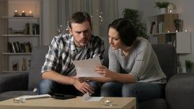 Λυπημένο ζεύγος που διαβάζει μια επιστολή στη νύχτα στο σπίτι απόθεμα βίντεο