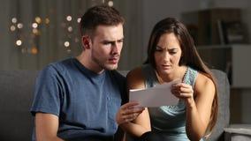 Λυπημένο ζεύγος που διαβάζει τις κακές ειδήσεις σε μια επιστολή στη νύχτα απόθεμα βίντεο