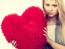 Λυπημένο κορίτσι που κρατά το μεγάλο κόκκινο μαξιλάρι στη μορφή καρδιών Στοκ φωτογραφία με δικαίωμα ελεύθερης χρήσης