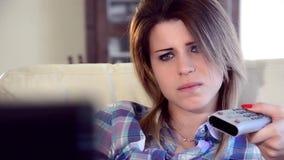 Λυπημένο κορίτσι που προσέχει τη TV απόθεμα βίντεο