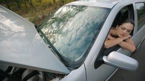 Λυπημένο κορίτσι στο σπασμένο αυτοκίνητο απόθεμα βίντεο
