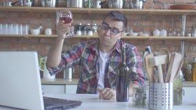 Λυπημένο κρασί κατανάλωσης ατόμων αγάμων στην κουζίνα και προσοχή ενός lap-top στοκ εικόνες