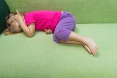 Λυπημένο μικρό κορίτσι που βρίσκεται στον καναπέ Στοκ εικόνα με δικαίωμα ελεύθερης χρήσης