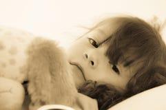 Λυπημένο μικρό κορίτσι που βρίσκεται στο κρεβάτι στα κλινοσκεπάσματα.  Στοκ φωτογραφία με δικαίωμα ελεύθερης χρήσης