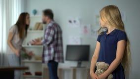 Λυπημένο μικρό κορίτσι που φαίνεται οι γονείς της που υποστηρίζουν στο υπόβαθρο, προβλήματα στην οικογένεια απόθεμα βίντεο