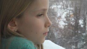 Λυπημένο παιδί που κοιτάζει στο παράθυρο, δυστυχισμένο στοχαστικό παιδί, πρόσωπο κοριτσιών, χιονίζοντας χειμώνας στοκ εικόνα