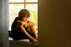Λυπημένο παιδί, αγόρι, που κάθεται σε μια ασπίδα παραθύρων στοκ εικόνες με δικαίωμα ελεύθερης χρήσης