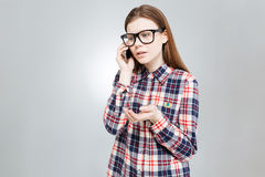 Λυπημένο όμορφο έφηβη που στέκεται και που μιλά στο τηλέφωνο κυττάρων Στοκ Φωτογραφία