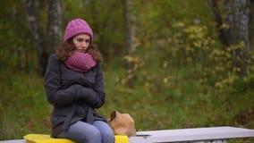 Λυπημένο όμορφο πάγωμα γυναικών στο πάρκο φθινοπώρου, κρύο φθινόπωρο Αισθάνεται κρύα και προσπαθεί να κρατήσει θερμός Σε αργή κίν απόθεμα βίντεο