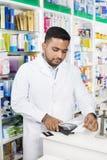 Λυσσασμένη έξω παραλαβή φαρμακοποιών από τον αναγνώστη στο φαρμακείο Στοκ φωτογραφίες με δικαίωμα ελεύθερης χρήσης