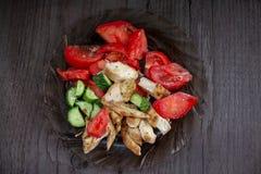 Λωρίδα κοτόπουλου με τις ντομάτες και τα αγγούρια στο μαύρο πιάτο γυαλιού Τοπ όψη Στοκ Εικόνες