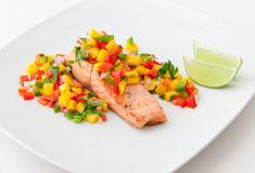 Λωρίδα σολομών με το salsa μάγκο στο άσπρο πιάτο. Στοκ Εικόνες
