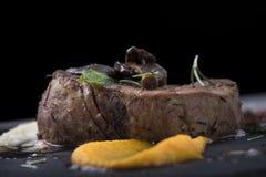 Λωρίδα βόειου κρέατος με τα μανιτάρια, τις ξηραμένες από τον ήλιο ντομάτες και το φυτικό πουρέ σε ένα πιάτο 8close πλακών επάνω σ Στοκ Εικόνες