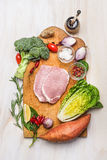 Λωρίδα οσφυϊκών χωρών χοιρινού κρέατος με την παραλλαγή των οργανικών λαχανικών: γλυκιά πατάτα, φύλλα σαλάτας, μπρόκολο, κρεμμύδι Στοκ φωτογραφίες με δικαίωμα ελεύθερης χρήσης