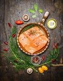 Λωρίδα σολομών στο τηγανισμένο τηγάνι με τα χορτάρια και τα συστατικά για το μαγείρεμα στο αγροτικό ξύλινο υπόβαθρο, τοπ άποψη Στοκ φωτογραφία με δικαίωμα ελεύθερης χρήσης