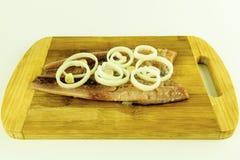 Λωρίδα των παστωμένων ρεγγών ένας στα ξύλινα τέμνοντα ψεκασμένα πίνακας WI Στοκ φωτογραφία με δικαίωμα ελεύθερης χρήσης