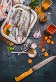 Λωρίδες ακατέργαστων ψαριών με το μαχαίρι κουζινών, καρυκεύματα και λαχανικά περικοπών, μαγειρεύοντας προετοιμασία στο σκοτεινό α Στοκ εικόνες με δικαίωμα ελεύθερης χρήσης
