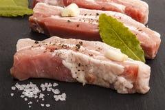 Λωρίδες κοιλιών χοιρινού κρέατος στην πλάκα με το φύλλο καρυκευμάτων και κόλπων Στοκ Φωτογραφίες