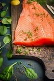 Λωρίδες σολομών στον τέμνοντα πίνακα και φρέσκα συστατικά για το μαγείρεμα Στοκ Φωτογραφία