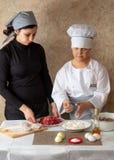 Μάγειρας αγοριών και μάγειρας μητέρων στην κουζίνα στοκ φωτογραφίες με δικαίωμα ελεύθερης χρήσης