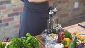 Μάγειρας αρχιμαγείρων που παίρνει τον πράσινο μαϊντανό και την κοπή στον ξύλινο πίνακα Τέμνοντα χορτάρια μαγείρων αρχιμαγείρων γι απόθεμα βίντεο