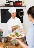 Μάγειρας και σερβιτόρα στην κουζίνα cafe's Στοκ Εικόνες