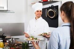 Μάγειρας και σερβιτόρα στην κουζίνα cafe's Στοκ Φωτογραφία