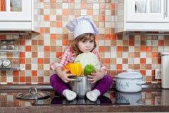 Μάγειρας κοριτσιών με τα φρέσκα λαχανικά Στοκ Εικόνα