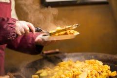 Μάγειρας με την τηγανισμένη πατάτα στο πιάτο και τον τορναδόρο Στοκ Εικόνες