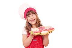 Μάγειρας μικρών κοριτσιών με τα γλυκά donuts Στοκ φωτογραφία με δικαίωμα ελεύθερης χρήσης