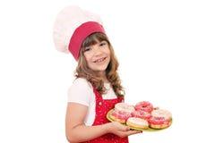 Μάγειρας μικρών κοριτσιών με τα γλυκά donuts Στοκ Φωτογραφίες
