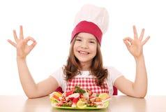 Μάγειρας μικρών κοριτσιών με τα θαλασσινά και τα εντάξει σημάδια χεριών Στοκ Εικόνα