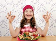 Μάγειρας μικρών κοριτσιών με τα burritos και τα εντάξει σημάδια χεριών Στοκ Φωτογραφίες