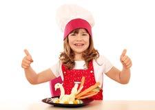 Μάγειρας μικρών κοριτσιών με τους αντίχειρες επάνω και το άσπρο διακοσμημένο κύκνος s Στοκ Φωτογραφίες