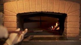 Μάγειρας που βάζει τη ζύμη πιτσών στο φούρνο τούβλου απόθεμα βίντεο