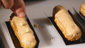 Μάγειρας που διακοσμείται ήπια με πρόσφατα ψημένος eclairs χρησιμοποιώντας τη μαρέγκα Ο ζαχαροπλάστης κάνει skillfully ένα μαγειρ απόθεμα βίντεο