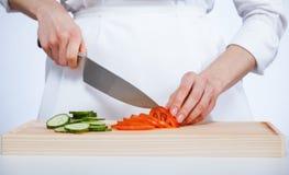 Μάγειρας που κόβει το φρέσκες αγγούρι και την ντομάτα Στοκ φωτογραφία με δικαίωμα ελεύθερης χρήσης