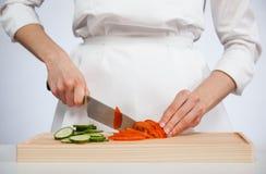 Μάγειρας που κόβει το φρέσκες αγγούρι και την ντομάτα Στοκ φωτογραφίες με δικαίωμα ελεύθερης χρήσης