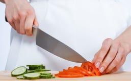 Μάγειρας που κόβει το φρέσκες αγγούρι και την ντομάτα Στοκ Φωτογραφίες