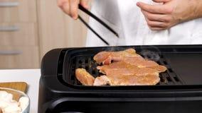 Μάγειρας που προετοιμάζει το ψημένο στη σχάρα κρέας σε μια σχάρα στην κουζίνα απόθεμα βίντεο