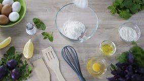 Μάγειρας που προσθέτει το αλεύρι στο κύπελλο γυαλιού, που προετοιμάζεται για την κατασκευή των κέικ, αρτοποιείο απόθεμα βίντεο