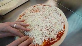 Μάγειρας που προσθέτει το τυρί στη ζύμη πιτσών απόθεμα βίντεο