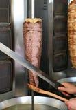 Μάγειρας που τεμαχίζει το τουρκικό αρνί Doner Kebab με ένα αιχμηρό ξίφος όπως το μαχαίρι Στοκ Εικόνα